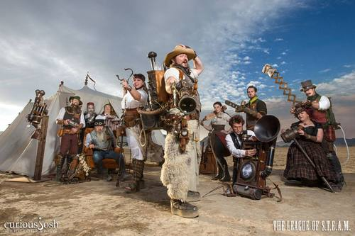 Photo of a group of people in a desert in steampunk outfits.